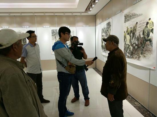 电视台记者采访参观画展的老军垦  崔文魁摄